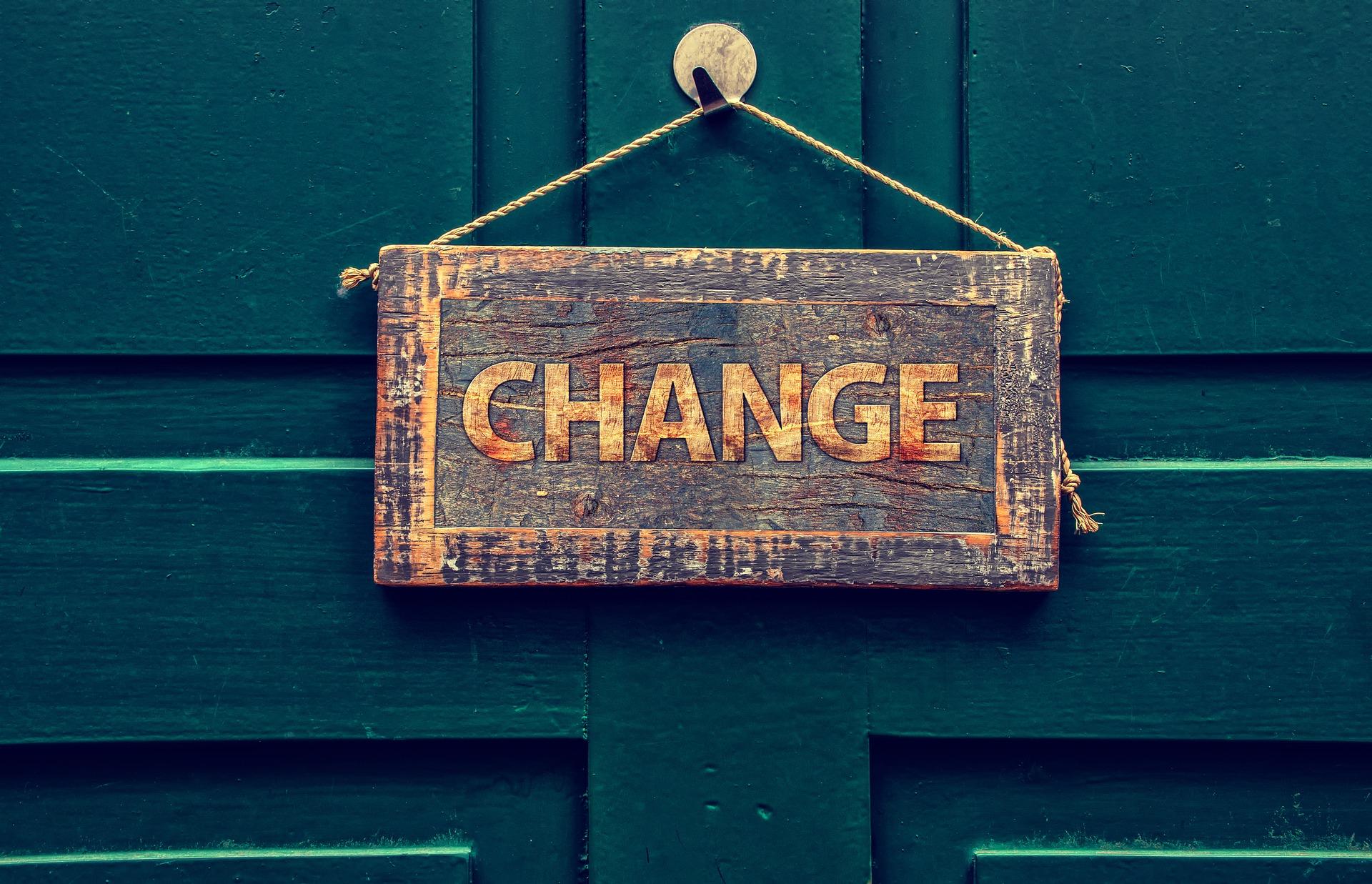 Ξύλινη μπλε πόρτα με διακοσμητική ταμπέλα που γράφει change